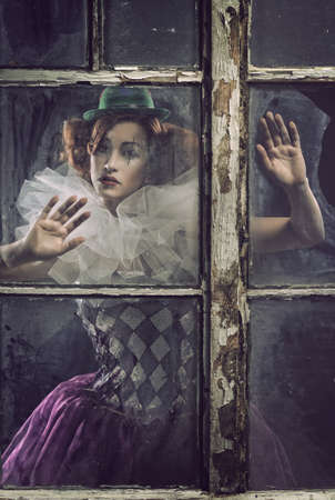 A lonely sad pierrot woman behind the glass photo