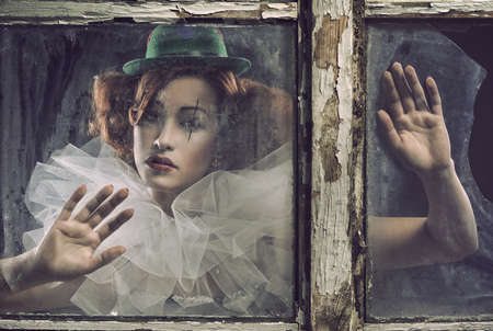 pierrot: A lonely sad pierrot woman behind the glass