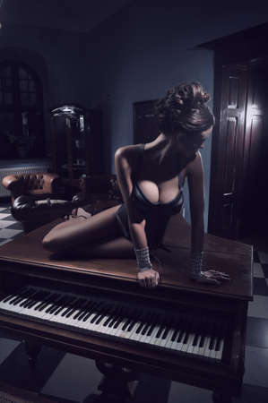 concert hall: Sexy actress laying on a piano Stock Photo