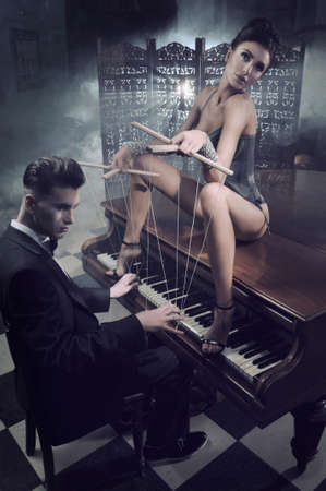 Sensual woman in sexy lingerie sitting on a piano photo