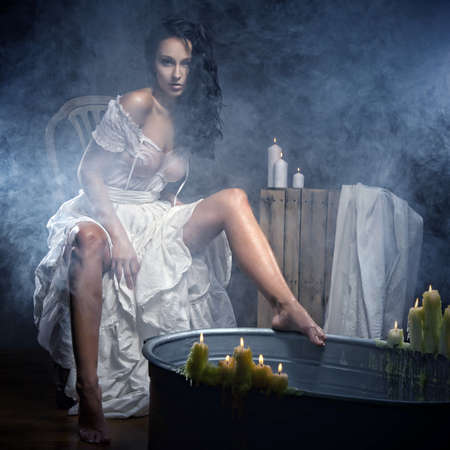 Woman relaxing in bath with candels photo