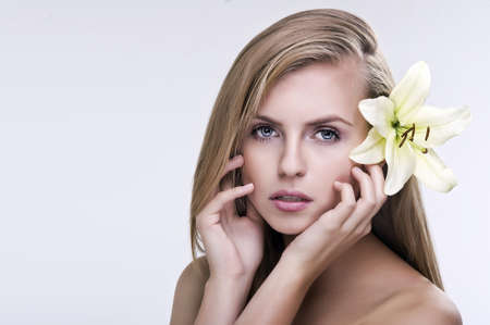 Beauty face of the young beautiful woman with flower  Female touching skin  photo