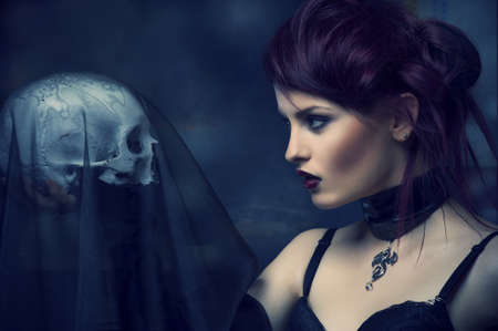 bracelet tattoo: Young alternative woman with a skull  Stock Photo