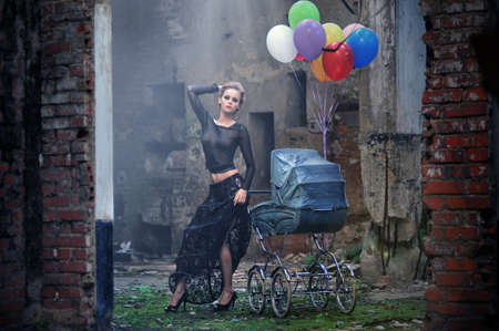 Young sexy woman with balloons and baby carriage photo