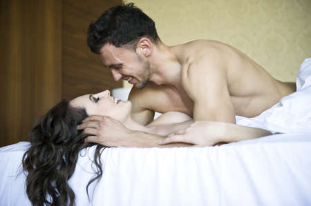 erotic couple: Young lovers lay in bed
