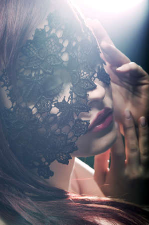 lace up: beautiful woman with red lips and lace mask over her eyes Stock Photo