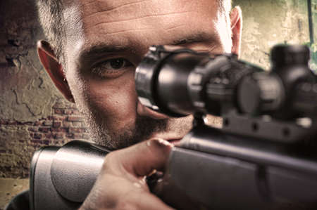 Portrait of serious man aiming with gun photo
