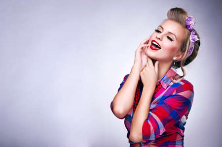 Beautiful young woman with pin-up make-up and hairstyle posing photo