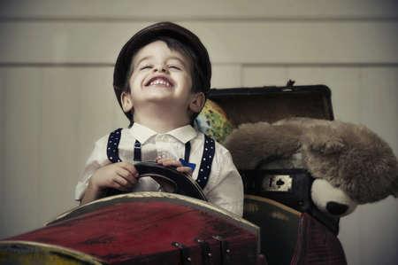 Jonge gelukkige jongen in houten auto Stockfoto