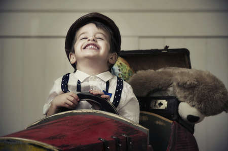 child s: Young happy boy in wooden car