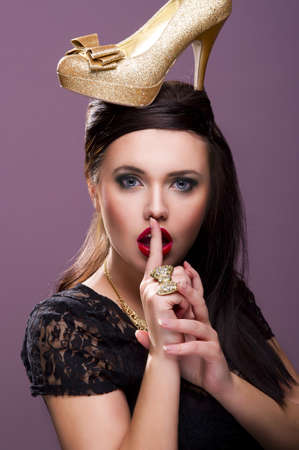 Sexy woman with gold shoe on head photo