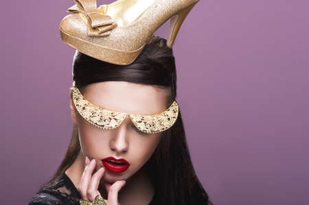 Sexy woman woth gold shoe on head photo