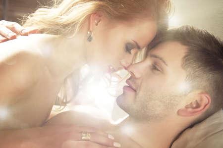 personas desnudas: Sexy joven pareja bes�ndose y jugando en la cama Foto de archivo