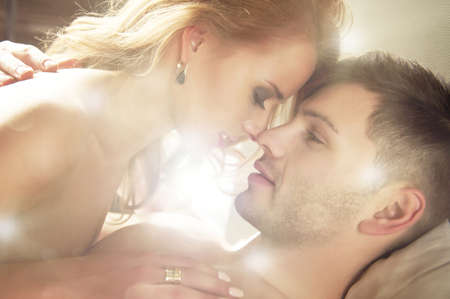 Sexy young couple kissing and playing in bed Stock Photo - 21375102