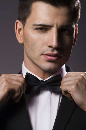 Close-up portrait of a young handsome man with bow tie photo
