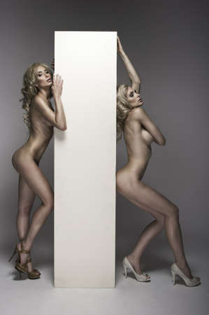 Two beautiful naked women with board