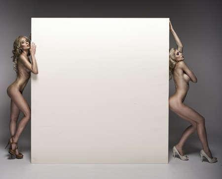 naked: Twee mooie naakte vrouwen met board Stockfoto