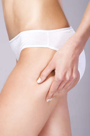 cellulite: Female squeezing cellulite skin on her buttock