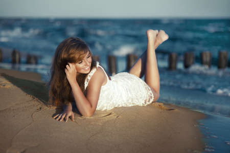 Happy beauty young woman lying on the beach photo