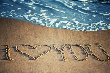 I love you - written in the sand with a foamy wave underneath photo