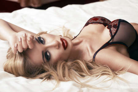 Beautiful young blonde woman in lingerie lying on the bed
