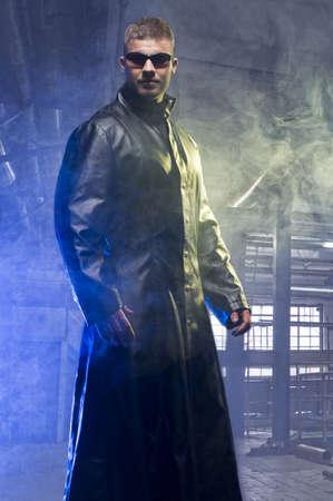 vampira sexy: Matrix Style Juego de roles Personaje hombre adulto en la capa en la antigua f�brica de Trench Foto de archivo