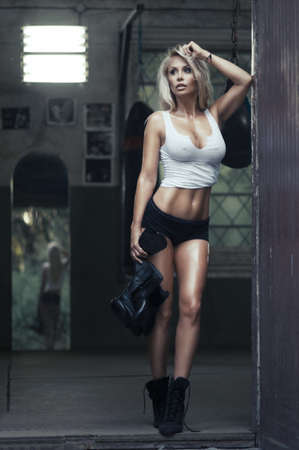 female fighter: Sexy blonde woman posing in boxing hall Stock Photo
