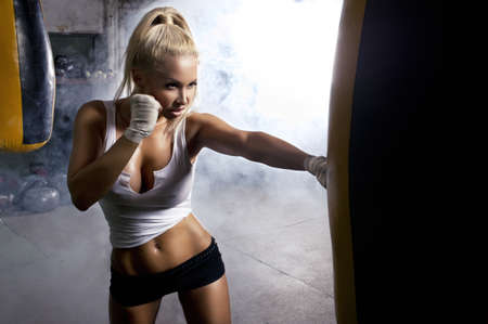 girl punch: Young woman fitness boxing in front of punching bag