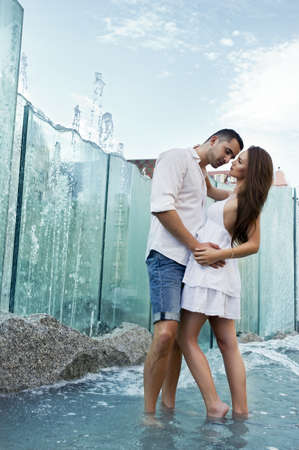 Couple in love kissing each other in fountain photo