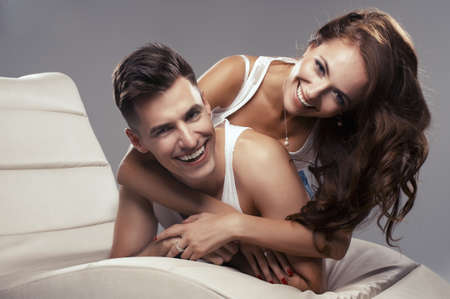 couple au lit: Jeune couple heureux serrant les uns les autres Banque d'images