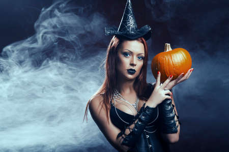 The serious girl is standing with the pumpkin in smoke photo