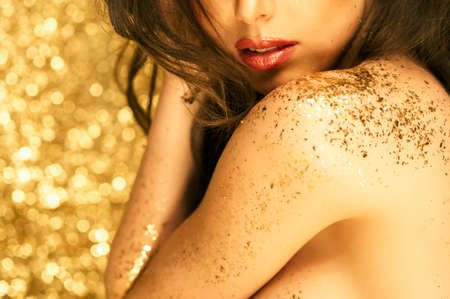 sparkles: Magic Girl Portrait in Gold. Golden Makeup Stock Photo