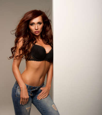 Beautiful sexy woman posing wearing jeans and bra  Long healthy brunette hair  photo