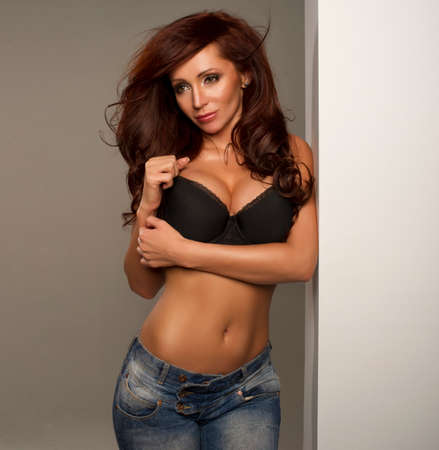 Sexy smiling woman in bra and jeans photo