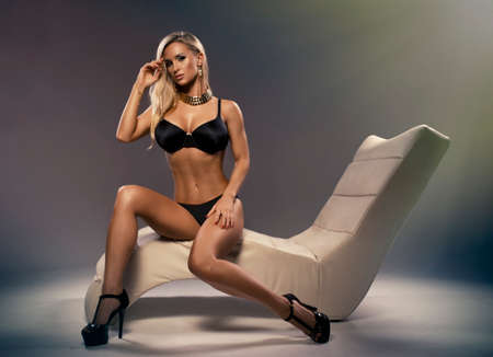 Sexy blonde woman sitting on a stylish leisure photo