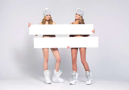 Two beauty woman only in hat and shoes with boards photo