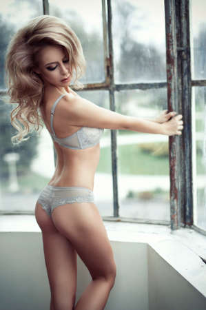 Sensual woman with perfect body wearing underwear posing, looking at camera. Long curly hair and beauty smile photo