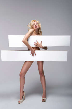 naked young woman: Beautiful young woman holding empty white board