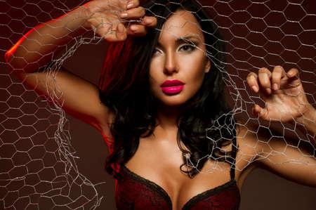 mujer de espaldas: Mujer atractiva detr�s de la cerca de alambre