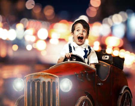 juguetes de madera: Sonrisa ni�o en coche de madera en la noche en la calle Foto de archivo