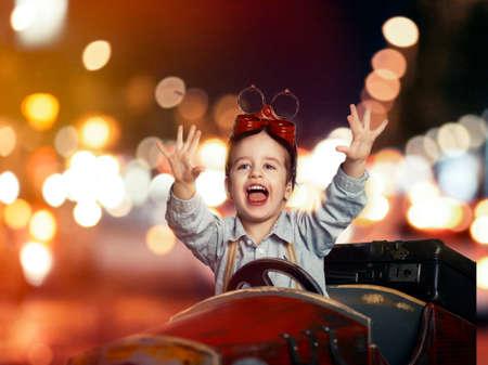 Sonrisa ni�o en coche de madera en la noche en la calle photo