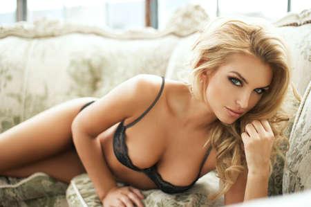 sexy girl nue: Sexy femme souriante d�tente dans son lit couvrant sa poitrine. Banque d'images