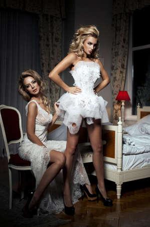 Zwei Freundinnen Spaß zu versuchen, auf einem Hochzeitskleid