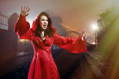 Elegant young witch in a red clothes cast magic spell in city Stock Photo - 26500535