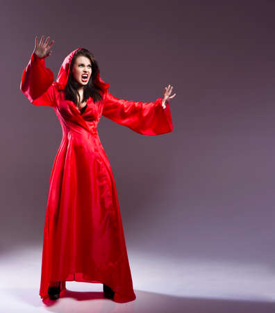Elegant young witch in a red clothes cast magic spell Stock Photo - 26500539