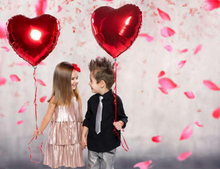 Happy kids with red heart balloon on a light  Stockfoto