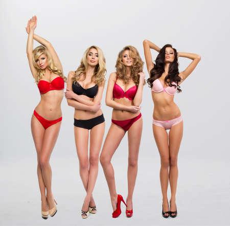 Schöne Frauen in vollem Wachstum stellen sich vor der Kammer in Dessous Standard-Bild - 31150287