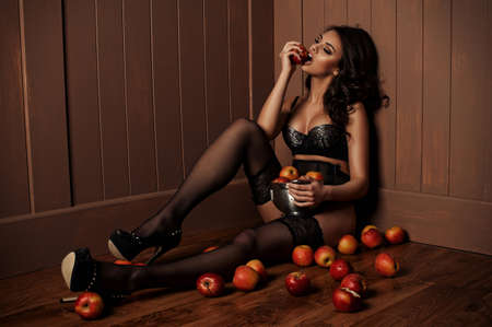 Sexy beautiful girl sitting on a floor with apple in the hand.