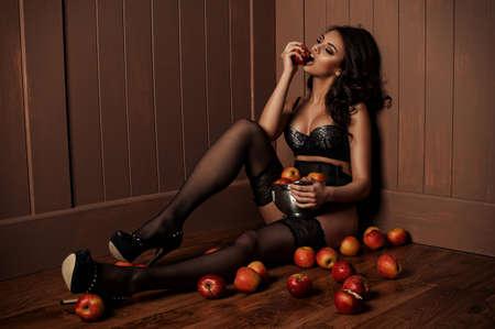Sexy mooi meisje zittend op een vloer met een appel in de hand.