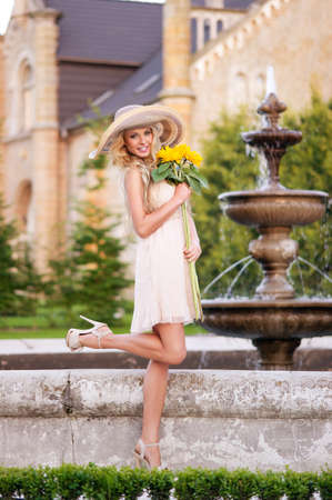 Beautiful young girl in light dress in the fabulous garden, holding bouquet of sunflowers photo